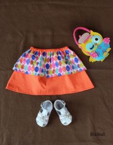 jupes à pans arc-en-ciel version orange, en taille 2 ans, présentée à plat avec chaussures et petit sac hibou