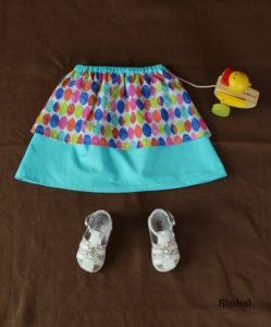 les jupes à pans version arc-en-ciel, présentée ici en bleu turquoise, en taille 4 ans