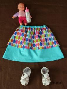 mise en scène de la jupe à pans bleue avec chaussures, bébé en plastique et biberon. Conception et fabrication française, à proximité de Nantes et Pornic