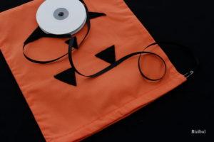 on insère le lien dans la coulisse du sac à bonbons d'Halloween à l'aide d'une épingle à nourrice